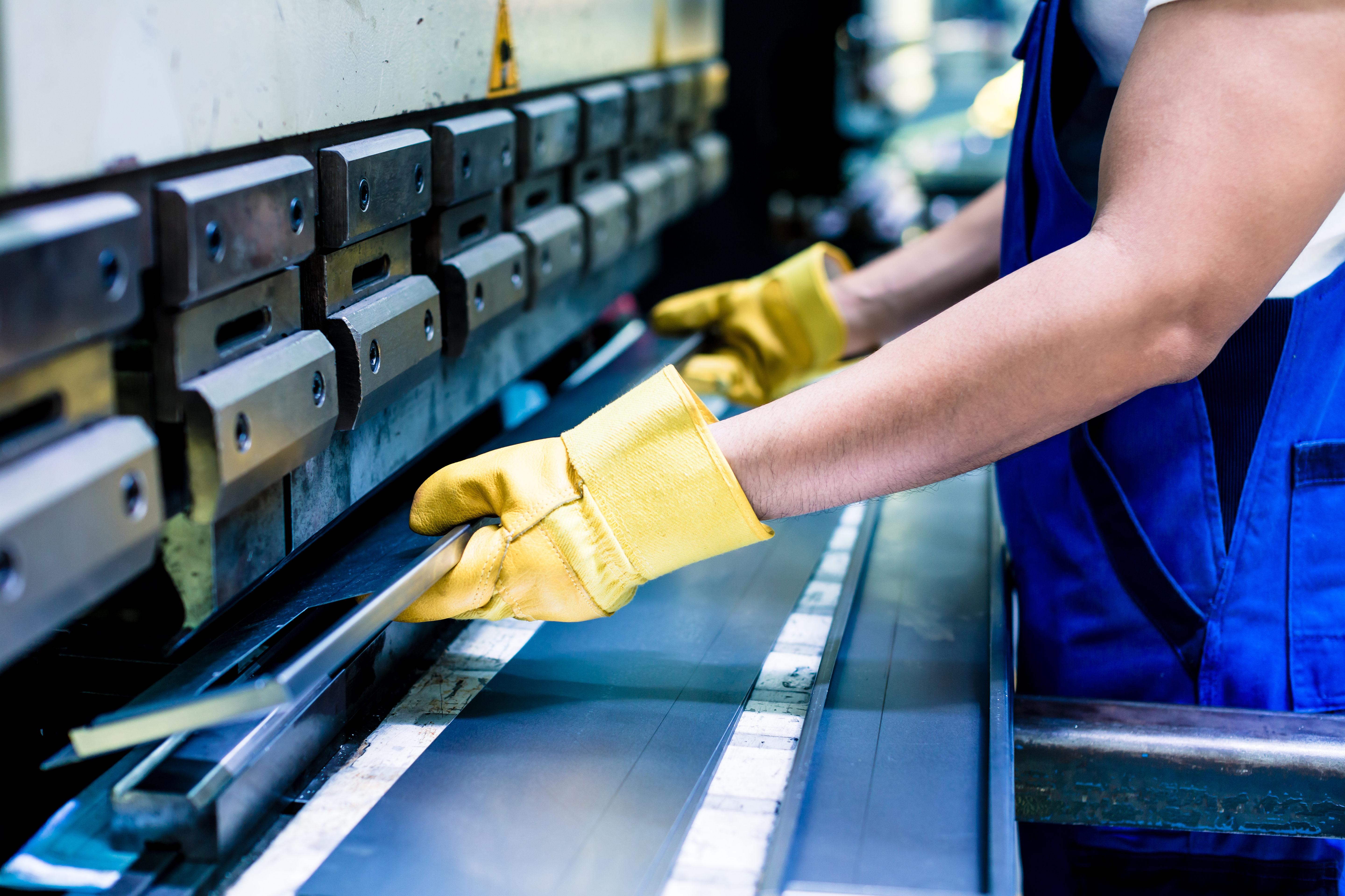 Worker placing the metal in the machine for pressing